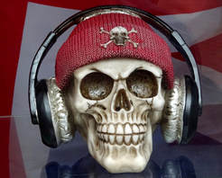 A plastic human skull in a red beanie with padded headphones on
